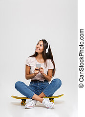 Portrait of young cheerful girl in white headphone chatting...