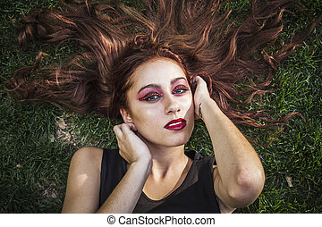 Portrait of young cheerful girl lying on the grass
