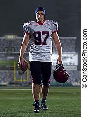 portrait of young confident American football player walking through the american football stadium field