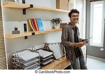 confident business entrepreneur in his office smiling to camera