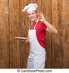 portrait of young cook man against a wooden wall