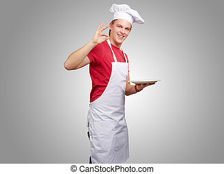 portrait of young cook man against a grey background