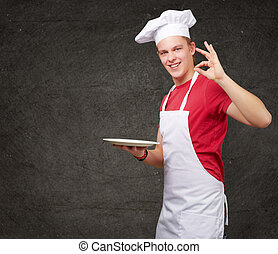 portrait of young cook man against a grunge wall