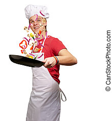 portrait of young cook man cooking vegetables on pan over...