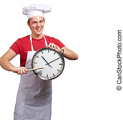 portrait of young cook man pointing a clock over white background