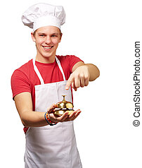 portrait of young cook man pressing a golden bell over white background