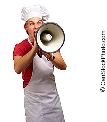 portrait of young cook man screaming with megaphone over white background