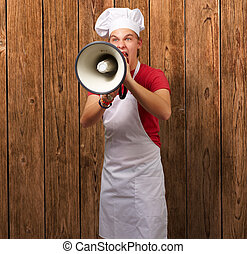 portrait of young cook man screaming with megaphone against a wooden wall