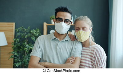 Portrait of young couple Arab man and Caucasian woman wearing face masks at home