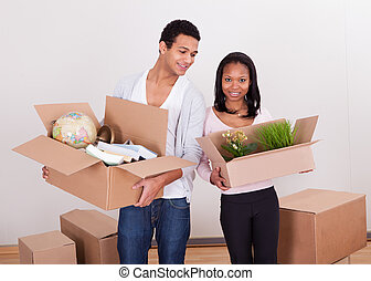Couple Carrying Boxes In House