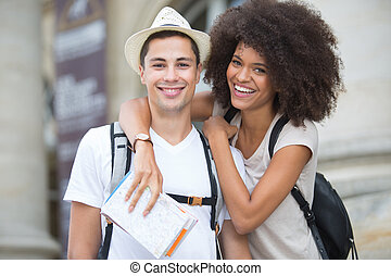 portrait of young couple holding map
