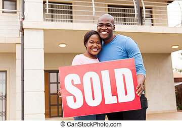 young couple holding sold sign
