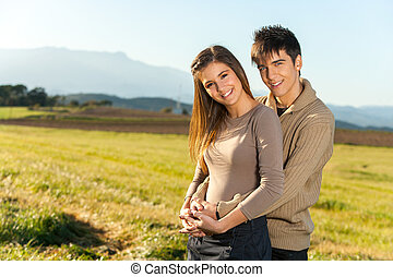 Portrait of young couple in countryside.