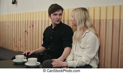 Portrait of young couple in love at a coffee shop, talking and kissing