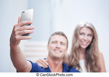 portrait of young couple  making selfie  with mobile phone. Focused on phone!