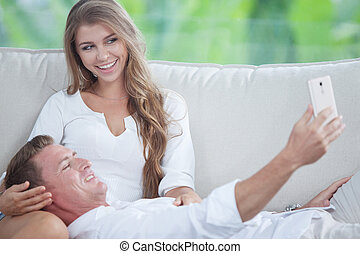 portrait of young couple  makingself photo with mobile phone
