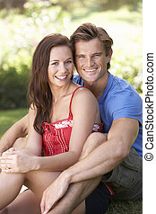 Portrait Of Young Couple Relaxing In Park
