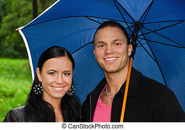 Portrait of young couple under umbrella in the park