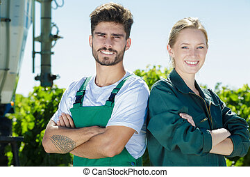 portrait of young couple working on vineyard