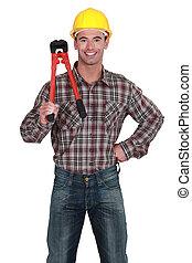 portrait of young craftsman holding adjustable spanner