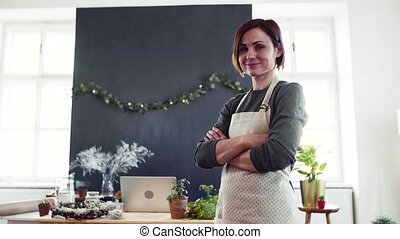 Portrait of young creative woman in a flower shop. A startup...