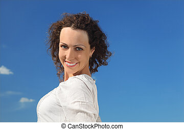 portrait of young curl beautiful woman smiling, blue sky