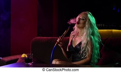 portrait of young curly blonde woman resting in the hookah room. Slow motion