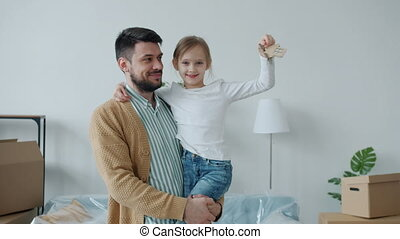 Portrait of young dad and cute daughter holding apartment keys smiling looking at camera standing indoors beautiful room. Family and relocation concept.