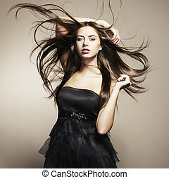 Portrait of young dancing woman with long flowing hair. Fashion