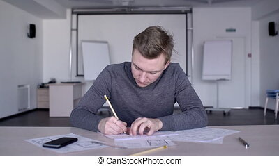 Portrait of young designer who works at desk with drawing, ruler and pencil.