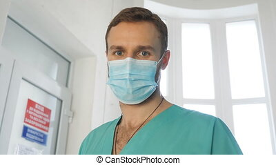 Portrait of young doctor take off medical face mask and ...