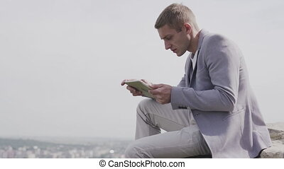 young dreamed businessman with tablet. He sits on a hump and works on a tablet.