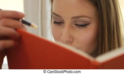 Portrait of young dreamy female student writing in the notepad close up