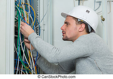 portrait of young electrician wiring an electric panel