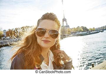 Portrait of young elegant woman on embankment in Paris,...