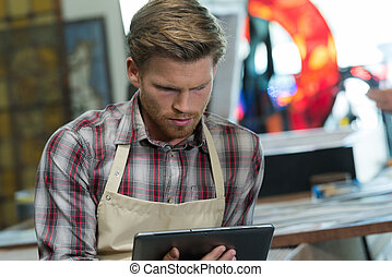 portrait of young factory worker operating tablet