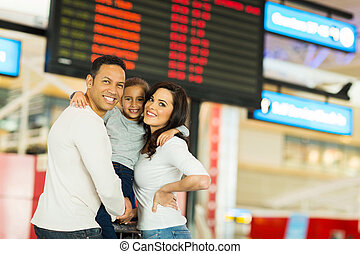 young family in front of flight information board at airport