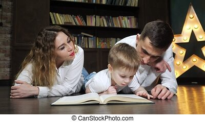 Portrait of young family mom, son and dad are reading a book together.