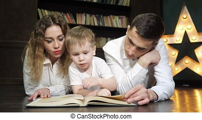 Portrait of young family mom, son and dad are reading a book...
