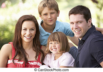 Portrait Of Young Family Relaxing In Park