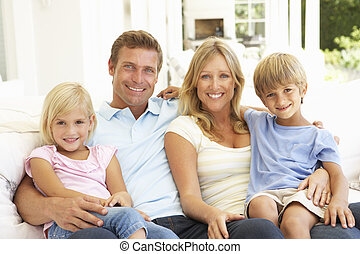 Portrait Of Young Family Relaxing Together On Sofa