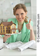 Portrait of young female architect holding model of house