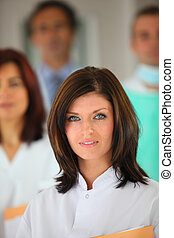 portrait of young female background with medical team in background