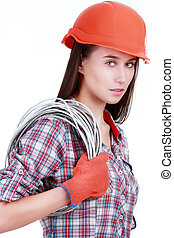 Portrait of young female builder in helmet with cabel on...
