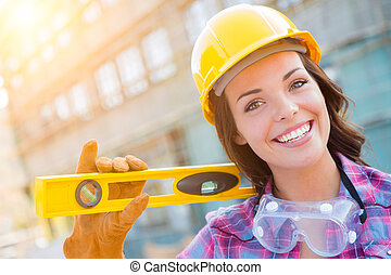 Portrait of Young Female Construction Worker with Level Wearing Gloves, Hard Hat and Protective Goggles at Construction Site.
