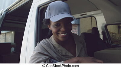 Portrait of young female van driver with a warehouse delivery