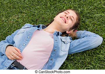 portrait of young female while lying in spring green garden