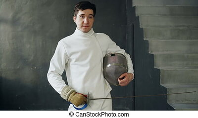 Portrait of young fencer man smiling and looking into camera...