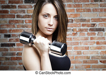 Portrait of Young fit woman lifting dumbbells and looking at...