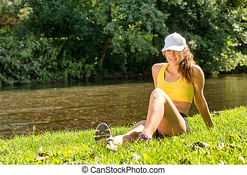 Portrait of young fit woman sitting on the grass